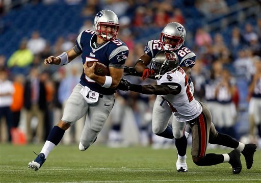 New England Patriots quarterback Tim Tebow runs past Tampa Bay Buccaneers defensive back Michael Adams as he's blocked by Patriots wide receiver Josh Boyce in a preseason game on Aug. 16, 2013, in Foxborough, Mass.