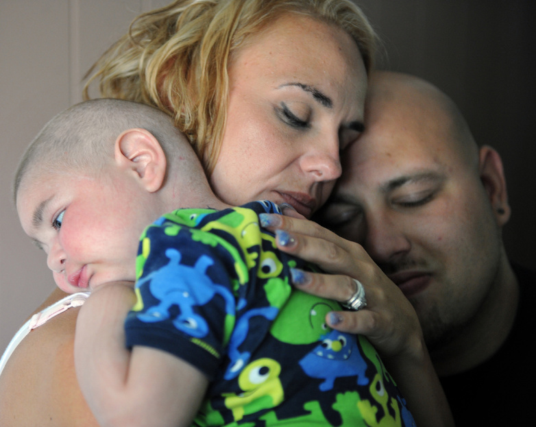 Christine Swidorsky holds her son, Logan Stevenson, 2, with her husband-to-be and Logan's father Sean Stevenson, for a portrait in their Jeannette, Pa., home July 30.