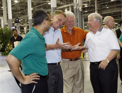 In this July 6, 2012, photograph, then-GreenTech Automotive executive Terry McAuliffe, second from left, jokes with former President Bill Clinton, center, and former Mississippi Gov. Haley Barbour, following the unveiling of the new electric MyCar at their manufacturing facility in Horn Lake, Miss. The big plans of eventually hiring a workforce of 25,000 people and eventually producing 1 million cars a year have been scaled back to a smaller facility to make 30,000 electric vehicles a year.