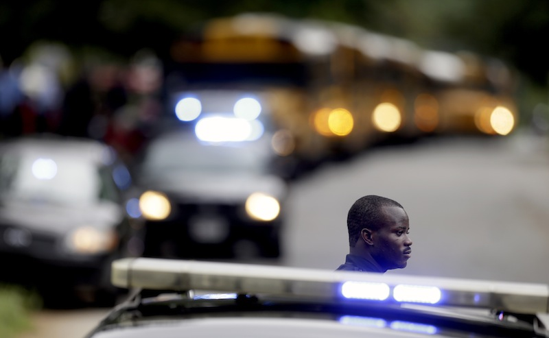 A Dekalb County Police officer stands guard as students from Ronald E. McNair Discovery Learning Academy board school buses to take them to reunite with their parents after they were evacuated after reports of a gunman entered the school, Tuesday, Aug. 20, 2013, in Decatur, Ga. All students and teachers are safe and a suspect is in custody after gunfire was heard at the Atlanta-area elementary school today. (AP Photo/David Goldman)