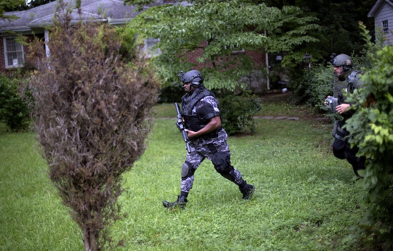 Dekalb County Police SWAT officers run though the front yard of a home toward Ronald E. McNair Discovery Learning Academy after reports of a gunman entered the school, Tuesday, Aug. 20, 2013, in Decatur, Ga. Superintendent Michael Thurmond says all students at Ronald E. McNair Discovery Learning Academy in Decatur east of Atlanta are accounted for and safe Tuesday and that he is not aware of any injuries. (AP Photo/David Goldman)