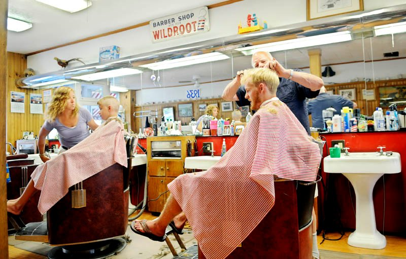 Gil Taylor, right, and Cole Allen get trims Thursday at Dom's Barber Shop in Hallowell from barbers Julie Keithley and Roland Marquis.