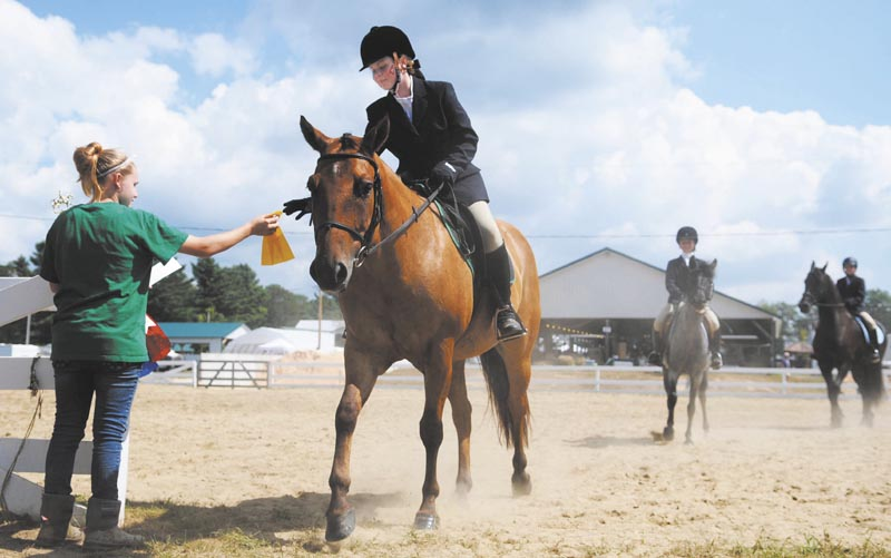 Katelyn MacMaster, left, hands Rayelyn Spencer a ribbon today during the 4-H horse show at the Windsor Fair. Several dozen riders showed off their steeds during the event, held on the fourth day of the annual agricultural exhibition.