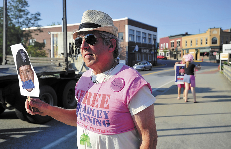 Mark Roman, 65, of Solon, stands on the Margaret Chase Smith Bridge in downtown Skowhegan with a picture of Bradley Manning on Wednesday. Roman and four other individuals stood on the bridge with signs to protest the Court Martial of former army enlisted man, Bradley Manning, for leaking documents to Wikileaks.