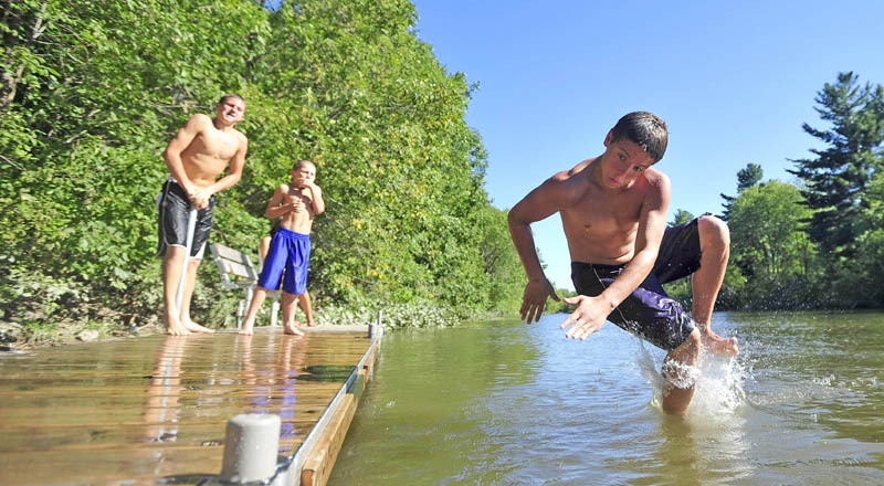 Anthony Visconti, 14, of Waterville, leaps in to the water from the dock on the Messalonskee Stream on North Street in Waterville on Saturday. The dock has become a popular place for locals to find respite from the heat.