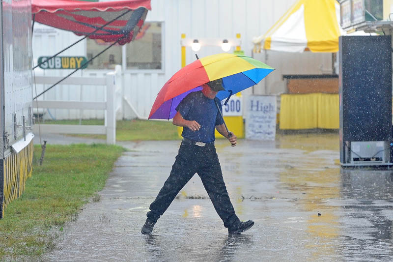 Tom Cowdry, of Oxford, tries to avoid a puddle as he walks around the 195th annual Skowhegan State Fair at the Skowhegan Fairgrounds on Friday. Cowdry, a 16-year ride operator at the Skowhegan State Fair, wound up playing bingo with other ride operators, as steady rain forced the rides to shut down.