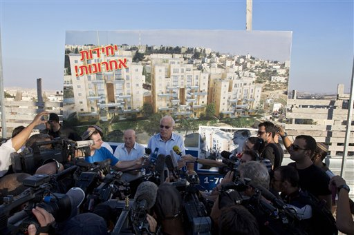 Israeli Minister of Housing and Construction Uri Ariel, center, speaks to journalists during a ceremony to mark the resumption of the construction of housing units in an east Jerusalem neighborhoodtoday. Israel's housing minister today gave final approval to build nearly 1,200 apartments in Jewish settlements, just three days before Israeli-Palestinian peace talks are to resume in Jerusalem. Hebrew on the sign reads