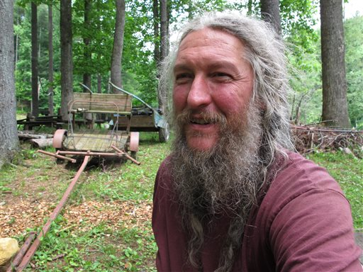 Eustace Conway sits near horse-drawn farm implements at his Turtle Island Preserve in Triplett, N.C., on June 27. People come from all over the world to learn natural living and how to go off-grid, but local officials ordered the place closed over health and safety concerns.