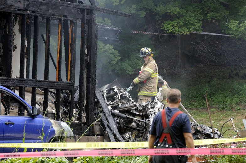 Firefighters work at the scene of a small plane crash Friday in East Haven, Conn.