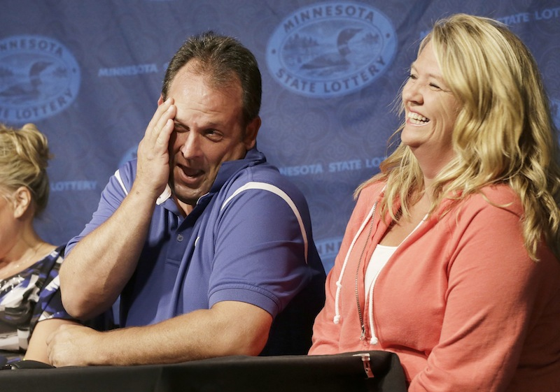 Paul White, of Ham Lake, Minn. gets a laugh from his girlfriend Kim VanRees, right, as he talked about his plans after he was announced as one of the winners of the $448.4 million Powerball Jackpot, Thursday, Aug. 8, 2013 in Minneapolis. White's share of the jackpot is $149.4 million. The woman at left is a co-worker friend. (AP Photo/Jim Mone)