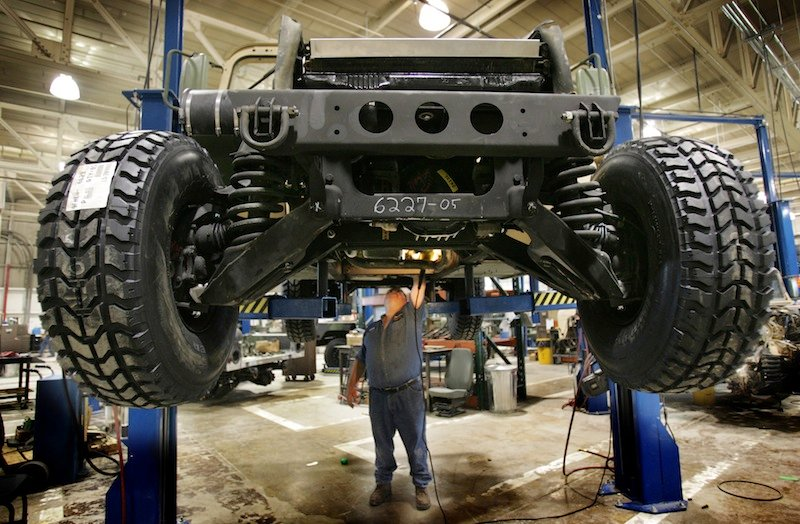 In this 2005 file photo, a mechanic inspects the underside of a refurbished Humvee at the Maine Military Authority in Limestone. The Maine Military Authority is laying off 140 people beginning in October because of the drawdown of troops and equipment in Iraq and Afghanistan. (AP Photo/Robert F. Bukaty)