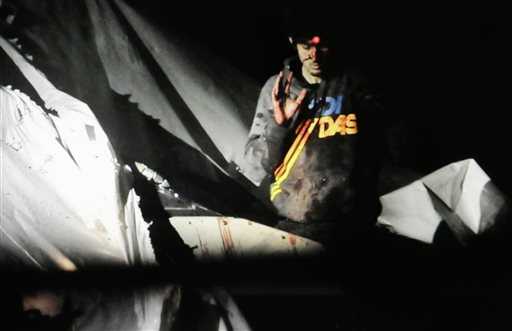 In this April 19, 2013, Massachusetts State Police photo, 19-year-old Dzhokhar Tsarnaev, bloody and disheveled with the red dot of a sniper's rifle laser sight on his forehead, raises his hand from inside a boat at the time of his capture by law enforcement authorities in Watertown, Mass.