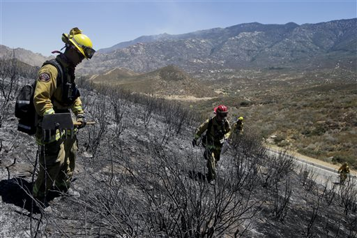 Firefighters look for hot spots as they walk through the scorched area on Friday near Banning, Calif. Southern California firefighters are facing another day of battle as they try to corral a wildfire that has destroyed 26 homes.