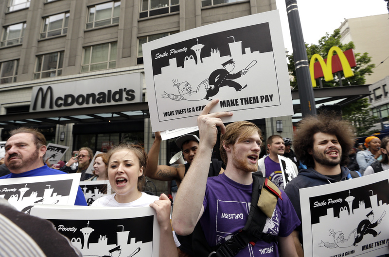 Demonstrators protesting what they say are low wages and improper treatment for fast-food workers stand near a McDonald's restaurant in downtown Seattle earlier this month.
