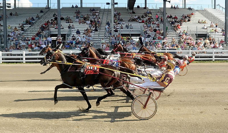 The pack passes the starting line in the Walter H. Hight Memorial Pace at the Skowhegan Fairgrounds on Saturday. Real Special won with a time of 1:54.1.