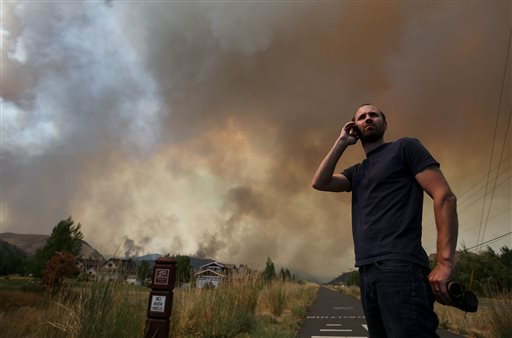 Kevin Bullock, of Bellevue, Idaho, watches smoke from the 64,000 acre Beaver Creek Fire on Friday, north of Hailey, Idaho. A number of residential neighborhoods have been evacuated because of the blaze.