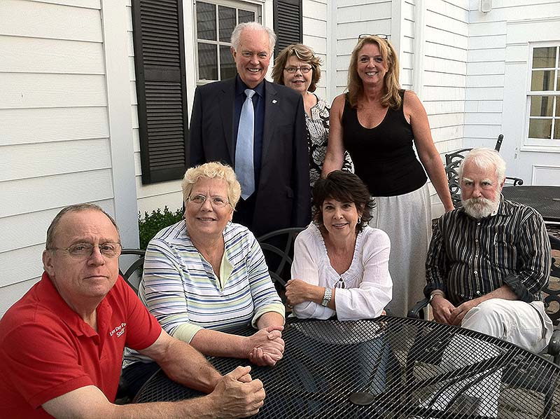 This Aug. 14, 2013, photo shows seven members of the Labor Day Parade Committee in Newtown, Conn. Seated from left are Tom D'Agostino, Robin Buchanan, Beth Caldwell and Dan Cruson. Standing from left are Brian Amey, Ellie Whalen and Stacey Olszewski. Caldwell, the head of the committee, believes they had found the right balance between respectful remembrance of the December shooting and celebration at the annual end-of-the-summer event that comes nearly nine months after shootings at Sandy Hook Elementary School left 26 dead, 20 of them children.
