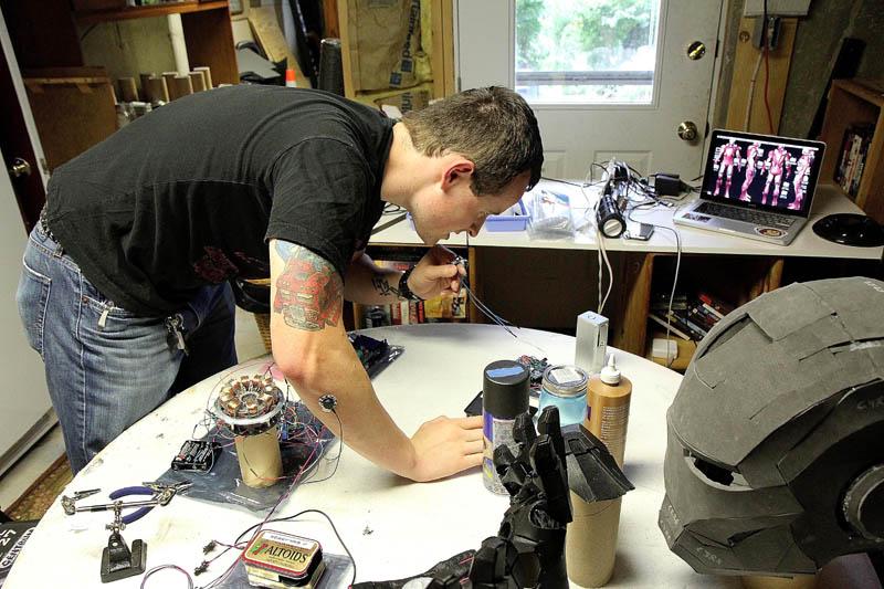 Thomas Lemieux works on a voice changer for his life-size Iron Man costume, in the basement of his Oakland home, recently.