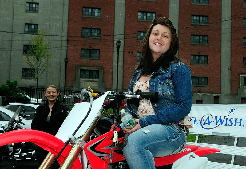 Kate McPherson, 17, of Litchfield, tries out the new Honda CRF 150 that she received during a Make-A-Wish Maine event on Saturday in the parking lot of the Fraternal Order of Eagles 3137 in Augusta.