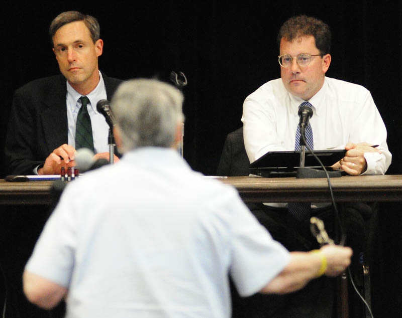 Public Utilities Commission members David Littell, left, and Mark Vannoy listen to Marguerite Lachance testify about smart meters during a hearing on Wednesday at Jewett Hall on the campus of University of Maine at Augusta.