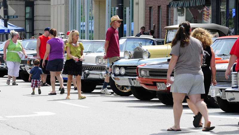 People look over a row of antique cars parked along Water Street today during AugustaFest 2013 in downtown Augusta. There was live music, food, art booths and a climbing wall set up a along the street and at the Augusta Waterfront Park.