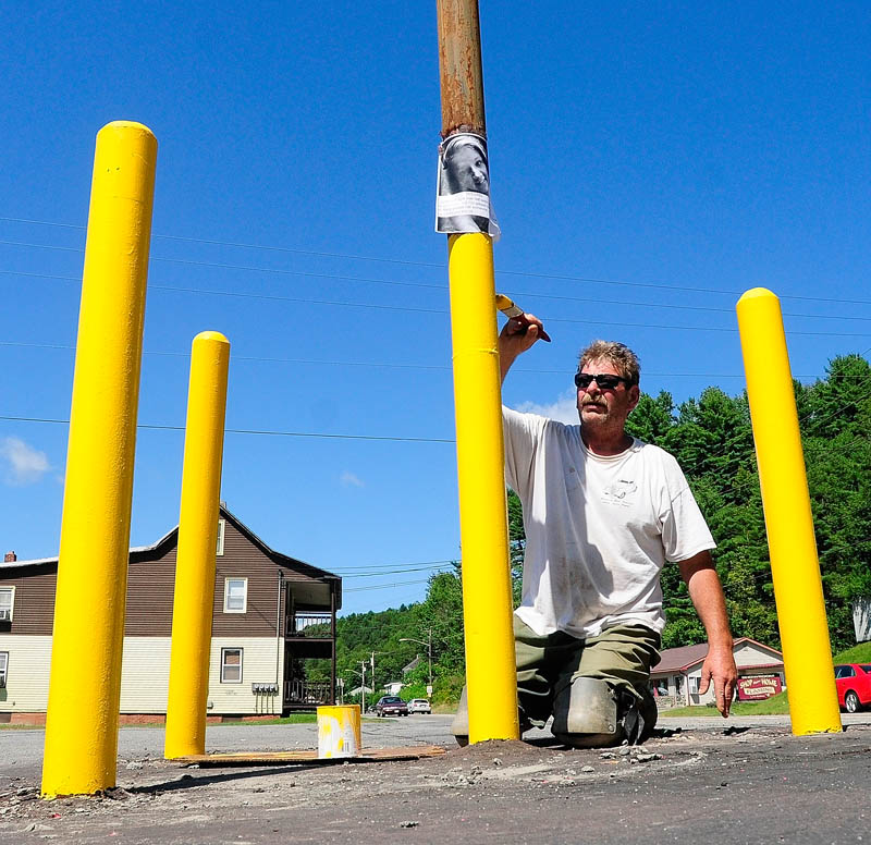 Bob Eldridge paints a sign post on Friday at College Carryout on Mount Vernon Avenue in Augusta. He said that he was going to paint the upper part black.