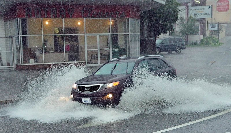A car splashes through a large puddle during a morning downpour today in front of Rotary Cleaners, near where Western Avenue ends at the Memorial Circle. Heavy rain overwhelmed storm drains and caused minor street flooding in several areas of the city.