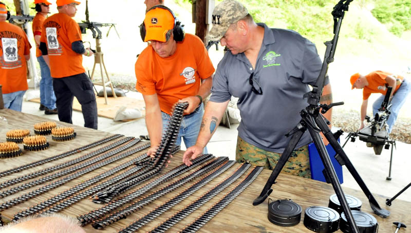 Andy Williams, right, and a volunteer load automatic weapons with ammunition belts during the Wounded Warriors Machine Gun Shoot in North Anson today. Williams hosts the event to bring veterans and gun enthusiasts together to socialize.