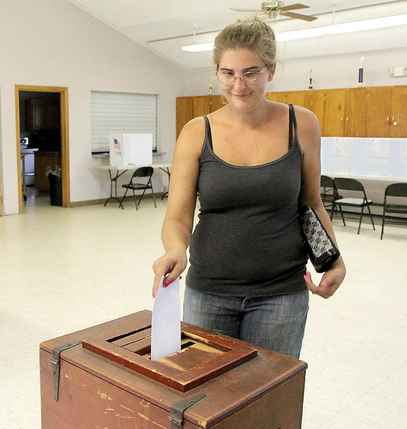 Clinton resident Stacey Reed casts her vote on the town's police department budget today.