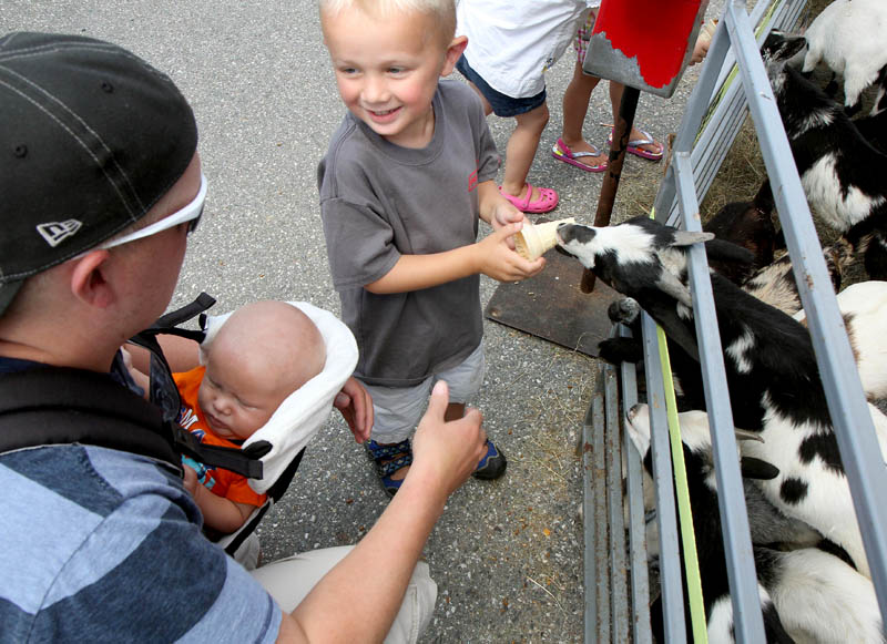 A miniature goat grabs a snack cone from three-year-old Jackson Munger of Pittsfield while at the the Taste of Greater Waterville on Wednesday. With Jackson is his dad Andrew and four-month-old brother Brantley.