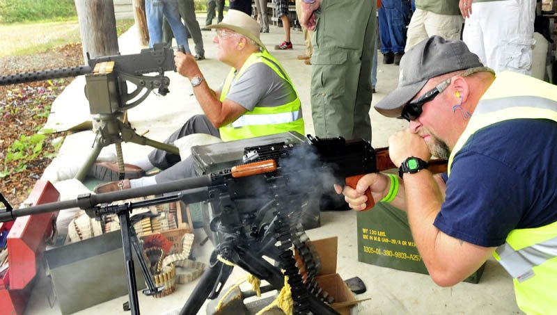 Nick Richards, right, of Winslow, fires a machine gun as Roland Marquis, of Augusta, prepares to fire another during the Wounded Warriors Machine Gun Shoot at the Williams Machine Gun Range in North Anson today.