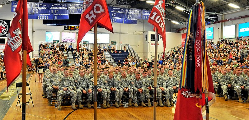 Flags and banners frame the troops during a send-off ceremony Saturday for the 133rd Engineer Battalion and the 1035th Survey and Design Team at the Portland Expo in Portland. The soldiers were chosen for a one-year deployment to Afghanistan.
