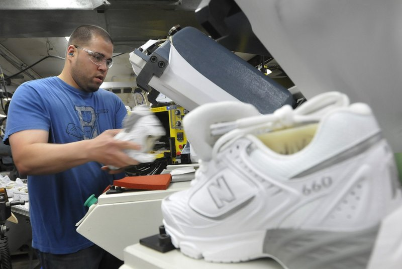 Justin Waring lays soles on shoes at New Balance factory in Norridgewock in 2011. New Balance – the only large sneaker manufacturer that still makes shoes domestically – employs about 900 in Maine.