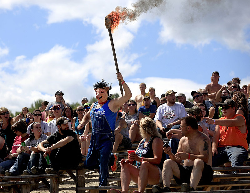 "Leslie Strought carries the ""Olympic torch"" into the pit in Hebron on Saturday to start the Redneck (Blank) Games. The three-day extravaganza celebrates the redneck lifestyle, one that embodies self-reliance, simplicity and the outdoors."