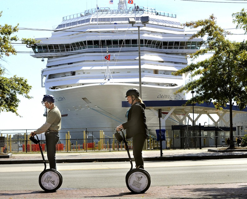 In this September 2012 file photo, a Segway tour passes in front of the Carnival Glory cruise ship, which was visiting Portland. Carnival, whose vessels frequent the city, will use a new exhaust gas cleaning system on 32 of its ships over the next three years.
