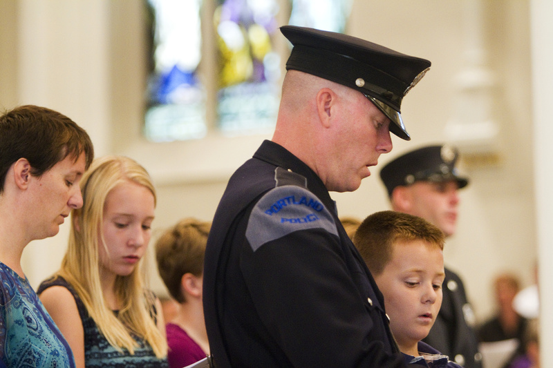 Portland Police Officer Kevin Haley and his son William, 9, participate in the Blue Mass at the Cathedral of the Immaculate Conception in Portland on Sunday. Hundreds of local, state and federal law enforcement officers, firefighters and emergency personnel were recognized for their dedication and self-sacrifice at the annual Mass.