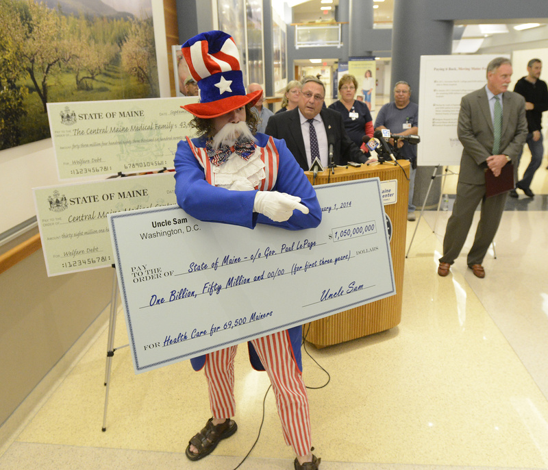 Gov. Paul LePage is interrupted by protester Paul Nickerson, dressed as Uncle Sam, during a news conference as LePage presents Central Maine Medical Center in Lewiston with a check for $38 million Wednesday.