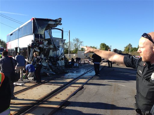 Officials respond to the scene where a city bus collided with a Via Rail passenger train at a crossing in Ottawa, Ontario, Wednesday. An Ottawa Fire spokesman said there are