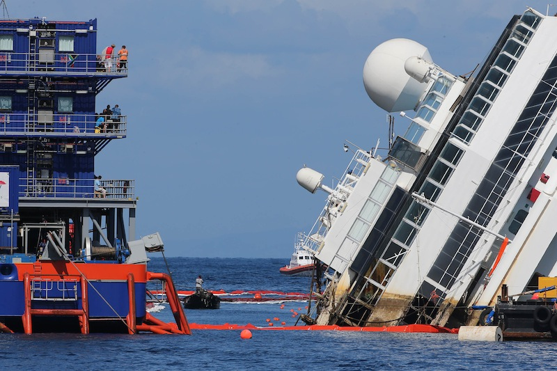 The Costa Concordia ship lies on its side on the Tuscan Island of Giglio, Italy, Monday, Sept. 16, 2013. Engineers on Monday succeeded in wresting the hull of the shipwrecked Costa Concordia from the Italian reef where it has been stuck since it capsized in January 2012, leaving them cautiously optimistic they can rotate the luxury liner upright and eventually tow it away. Never before has such an enormous cruise ship been righted, and the crippled Concordia didn't budge for the first three hours after the operation began, engineer Sergio Girotto told reporters. (AP Photo/Andrea Sinibaldi, Lapresse)