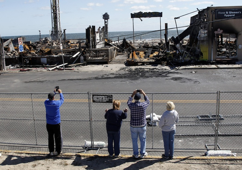 People take photographs of the charred rubble in Seaside Park, N.J., Tuesday, Sept. 17, 2013, after a fire last Thursday that started near a frozen custard stand in Seaside Park, quickly spread north into neighboring Seaside Heights. More than 50 businesses in the two towns were destroyed. The massive boardwalk fire in New Jersey began accidentally, the result of an electrical problem, an official briefed on the investigation said Tuesday. (AP Photo/Mel Evans)