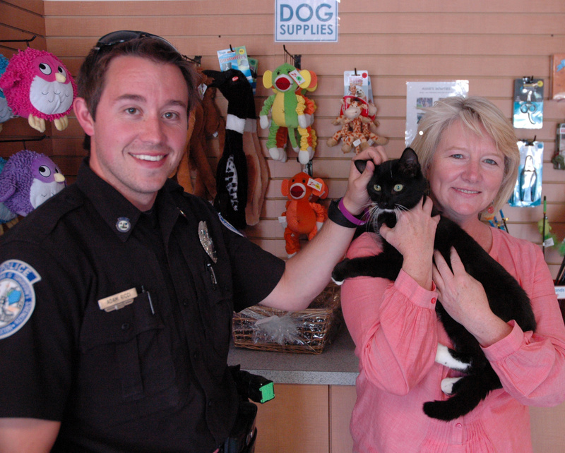 Buxton police Officer Adam Ricci pets Echo, one of many animals he has helped rescue, as Betsy Murphy, executive director of the Animal Refuge League of Greater Portland, holds the cat in the lobby of the Westbrook shelter. Buxton animals rescued