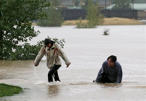 A couple plays in flood water at Utah Park in Aurora, Colo., on Thursday.