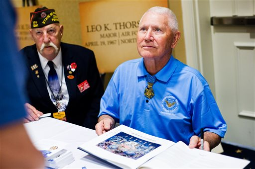 Major Leo K. Thorsness gets ready to sign a book for a fan on Thursday at the Gettysburg, Pa., conference. Thorsness, a Medal of Honor recipient, served in the Air Force in Vietnam. At left is State Sr. Vice Commander Gary R. Smith of Pennsylvania Veterans of Foreign Wars.