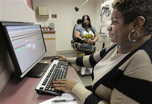 Jacqueline Saulsberry, a service coordinator at the Illinois Eye Institute, gathers information from patient Shameka Lewis-Coolidge during an appointment in Chicago. The institute, which will help with Obamacare enrollment in the Chicago area, plans to train a dozen staffers for the task.