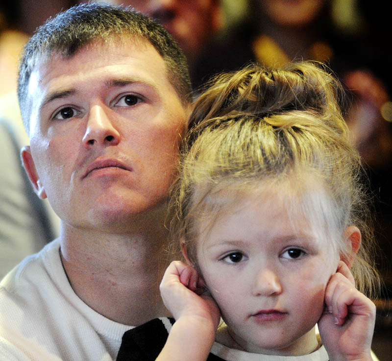 Travis Bentley holds his daughter, Reese, Tuesday during the first graduation ceremony for veterans at the Co-Occuring Disorders Court and Veterans Court at Kennebec County Superior Court in Augusta. Bentley, a Marine combat veteran of Iraq, graduated with Daniel Andrews, an Army combat veteran of Iraq.