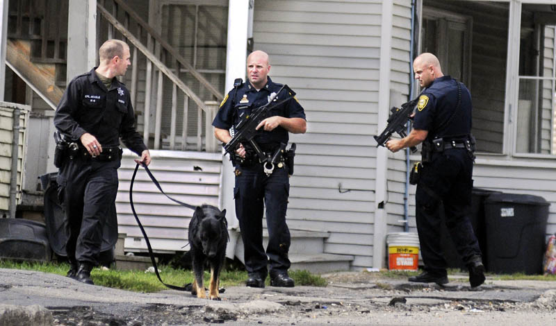Cpl. G.J. Neagle of the Kennebec County Sheriff's Office, left, today attempts to track a man allegedly carrying a gun with his dog on Mount Vernon Avenue in Augusta, aongside Augusta police officers Don Whitten, center, and Peter Cloutier. Police gave chase following an alleged robbery on Boothby Street.