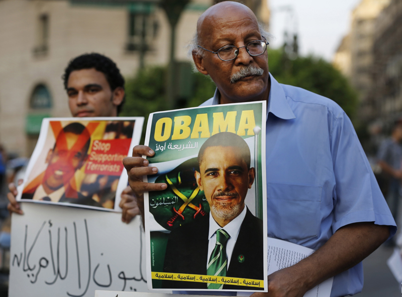 A demonstrator holds a placard mimicking U.S. President Barack Obama during a protest against possible U.S. forces' strike in Syria, in Cairo, Egypt, Sunday. The Arabic under Obama's name reads,