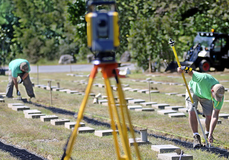 Josh Luce, right, uses satellite coordinates to mark headstones that Nick Cushman set Monday at the Maine Veterans' Memorial Cemetery in Augusta. The Farley & Son Landscaping employees reset several hundred stones at the cemetery.