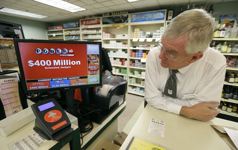 Dahl's grocery store manager Don Mark looks at a monitor displaying the estimated jackpot amount for Wednesday's Powerball drawing, Tuesday, Sept. 17, 2013, in Des Moines, Iowa. The giant Powerball jackpots keep coming, with the latest $400 million prize ranking among the largest ever. But soon, lottery players could see even more huge jackpots as organizers of the Mega Millions lottery move ahead with plans to revamp the game and attract more players. (AP Photo/Charlie Neibergall)