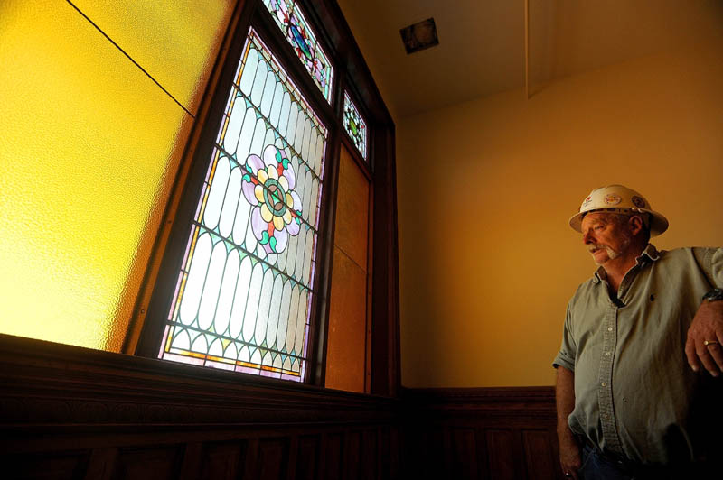 Homer Salisbury, site supervisor for Sheridan Construction, stands next to original, stained glass windows which illuminate the grand staircase in the Gerald Hotel in downtown Fairfield on Sept. 18.